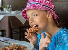 La ragazza turistica mangia il grande gamberetto in caffè sulla penisola di Sithonia Immagini Stock