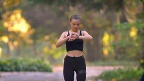 La ragazza in tuta con le cuffie che corre nel parco autunnale, smette di controllare l'orologio e continua a pareggiare video d archivio