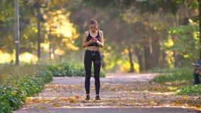 La ragazza in tuta con le cuffie che corre nel parco autunnale, smette di esaminare lo smartphone e continua a pareggiare video d archivio