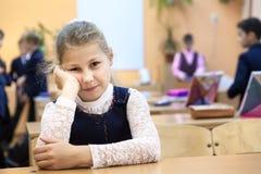 La ragazza un allievo è in un cattivo carattere sulla cavità mentre altri bambini che giocano sul fondo Fotografie Stock Libere da Diritti