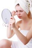 La ragazza in un asciugamano sulla sua testa, vede il suo fronte nello specchio fotografia stock