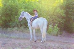 La ragazza in un cappello si siede su un cavallo Immagine Stock