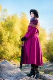 La ragazza in un cappotto cremisi luminoso esamina la distanza Fotografie Stock Libere da Diritti