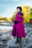 La ragazza in un cappotto cremisi luminoso esamina la distanza Fotografie Stock