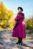 La ragazza in un cappotto cremisi luminoso esamina la distanza Fotografia Stock