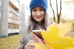 La ragazza in un cappotto ed in un cappello blu su un fondo degli alberi e delle foglie di acero di autunno fotografia stock