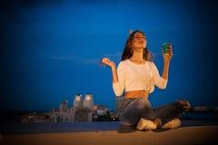 La ragazza in un cappuccio celebratorio respira l'aria fresca della notte fotografia stock libera da diritti