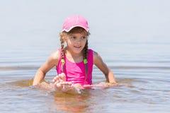 La ragazza in un cappuccio si siede sul fiume basso in acqua Immagine Stock Libera da Diritti