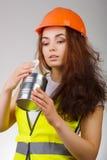 La ragazza in un casco ed in una maglia esamina il contenitore aperto del metallo Immagine Stock
