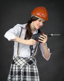 La ragazza in un casco impara utilizzare un trivello Fotografia Stock