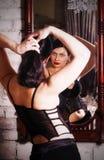 La ragazza in un corsetto davanti ad uno specchio corregge l'acconciatura Fotografie Stock Libere da Diritti