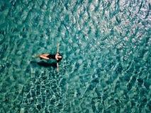 La ragazza in un costume da bagno nero nuota nel mare fotografia stock