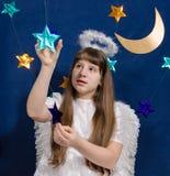 La ragazza in un costume di angelo gioca con le stelle Immagine Stock