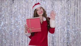 La ragazza in un costume nubile della neve tiene un regalo in sua mano ed ondeggia la sua mano, ciao Priorità bassa di Bokeh stock footage