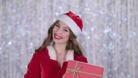 La ragazza in un costume nubile della neve tiene un regalo in sua mano ed ondeggia la sua mano, ciao Priorità bassa di Bokeh Movi archivi video