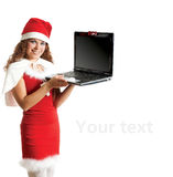 La ragazza in un costume Santa tiene il computer portatile nero Fotografie Stock