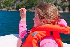 La ragazza in un giubbotto di salvataggio che si siede in una barca Immagini Stock