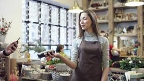 La ragazza in un grembiule dà il terminale per paing al compratore, lui paga con aiuto del suo telefono e lo ringrazia, quindi stock footage
