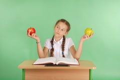 La ragazza in un uniforme scolastico che si siede allo scrittorio e mangia le mele Fotografia Stock Libera da Diritti