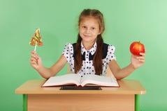 La ragazza in un uniforme scolastico che si siede allo scrittorio e sceglie la caramella o una mela Fotografie Stock Libere da Diritti