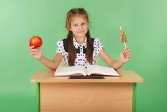 La ragazza in un uniforme scolastico che si siede allo scrittorio e sceglie la caramella o una mela Fotografia Stock