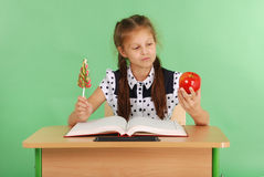 La ragazza in un uniforme scolastico che si siede allo scrittorio e sceglie la caramella o una mela Immagine Stock Libera da Diritti