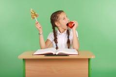 La ragazza in un uniforme scolastico che si siede allo scrittorio e sceglie la caramella o una mela Fotografia Stock Libera da Diritti