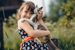 La ragazza in un vestito abbraccia un piccolo gatto immagini stock libere da diritti