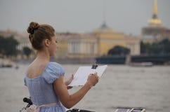 La ragazza in un vestito blu disegna il paesaggio urbano Immagini Stock Libere da Diritti