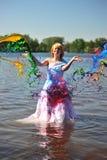 La ragazza in un vestito da cerimonia nuziale ha versato da una vernice Fotografie Stock Libere da Diritti