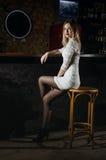 La ragazza in un vestito ed in un collant si siede nella barra Immagine Stock