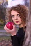 La ragazza in un vestito nero con la mela rossa fotografia stock