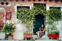 La ragazza in un vestito passeggia da un vecchio cortile accogliente immagini stock libere da diritti