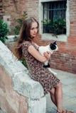 La ragazza in un vestito passeggia da un vecchio cortile accogliente immagini stock
