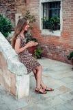 La ragazza in un vestito passeggia da un vecchio cortile accogliente fotografia stock