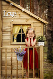 La ragazza in un vestito rosso posa in una casa sull'albero Immagine Stock