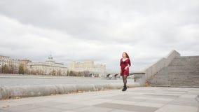 La ragazza in un vestito rosso sta camminando lungo la passeggiata stock footage