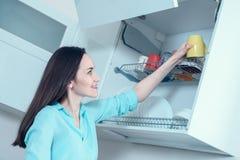 La ragazza in una camicia del turchese mette una tazza gialla sullo scaffale di secchezza dell'armadietto della cucina fotografia stock