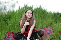 La ragazza in una camicia a quadretti rossa sta sedendosi su una coperta a quadretti rossa che mostra i pollici su su un fondo di immagini stock libere da diritti