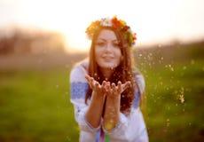 La ragazza in una corona del fiore sulla sua testa soffia via la lanugine da ciao fotografia stock libera da diritti