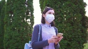 La ragazza in una maschera medica protettiva sul suo fronte va ed utilizza il telefono stock footage