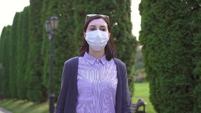 La ragazza in una maschera medica sul suo fronte è nel parco, Mo lento stock footage