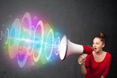 La ragazza urla in un altoparlante ed in COM variopinta del fascio di energia Immagine Stock
