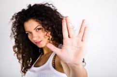 la ragazza ?urly-dai capelli mostra il segno Immagine Stock Libera da Diritti