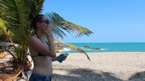La ragazza usa la protezione solare sulla spiaggia stock footage