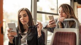 La ragazza utilizza un telefono cellulare nel bus della città immagini stock libere da diritti