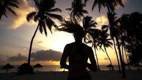 La ragazza va in giro di mattina nelle palme all'alba archivi video