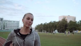 La ragazza va in giro lo stadio lungo la pedana mobile Atleta sui funzionamenti di atletica dopo la macchina fotografica archivi video