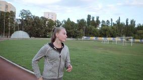 La ragazza va in giro lo stadio lungo la pedana mobile Movimento lento archivi video