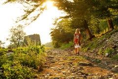 La ragazza va lungo il sentiero forestale al tramonto Immagini Stock